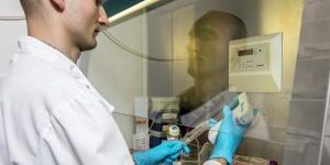 Researcher using a pipette in a fume hood
