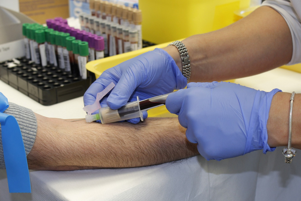 Healthcare professional taking a blood sample from an arm